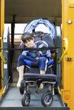男孩公共汽车残疾增强学校轮椅 免版税库存图片