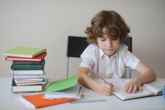 男孩努力地做他的坐在学校书桌的家庭作业 免版税库存图片
