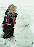 男孩努力地工作雕刻雪人 库存图片