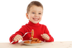 男孩叉子一点香肠微笑 图库摄影