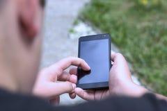男孩发与他的智能手机的一个正文消息 免版税库存图片