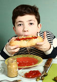 男孩叮咬自制巨大的热狗 免版税库存图片