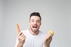 男孩吃一个红萝卜和苹果 免版税库存图片