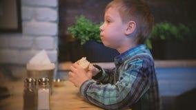 男孩吃一颗长方形宝石并且看在咖啡馆的电视 侧视图 股票视频