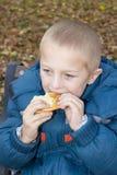 男孩吃两只手 免版税库存照片