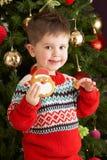 男孩吃前结构树年轻人的圣诞节曲奇&# 库存照片