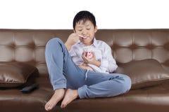 男孩吃在长沙发的冰淇凌 库存图片