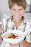 男孩吃家庭粥微笑 库存图片