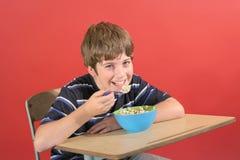 男孩吃年轻人的谷物服务台 库存图片