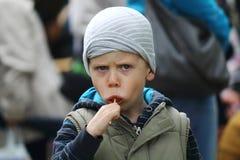 男孩吃棒棒糖 库存图片