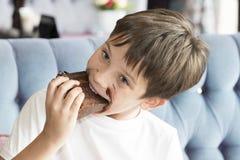 男孩吃着一块大蛋糕 免版税库存图片