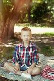 男孩吃着在夏天野餐的莓果 免版税库存照片