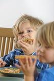 年轻男孩吃薄饼 图库摄影