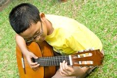 男孩吉他作用 免版税图库摄影