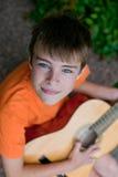 男孩吉他使用的一点 库存照片