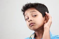 男孩听低声音 库存照片