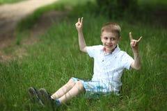 男孩听到在一种片剂的音乐在公园 库存图片
