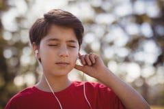 男孩听的音乐特写镜头在耳机的在障碍桩期间 免版税库存图片