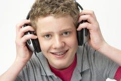 男孩听的音乐纵向微笑少年 免版税库存照片