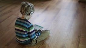 男孩听的音乐通过使用片剂个人计算机的耳机 影视素材