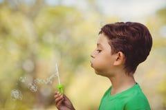 年轻男孩吹的泡影通过泡影鞭子 免版税图库摄影