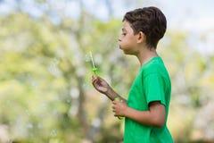 年轻男孩吹的泡影通过泡影鞭子 库存照片