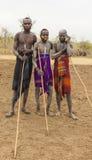 男孩和一个人从Mursi部落与矛在Mirobey村庄 图库摄影