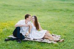 男孩和一个女孩一起坐白色饮用的茶的 免版税库存照片