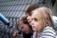 男孩和两个女孩在一台望远镜前面在铺磁砖的屋顶 库存照片