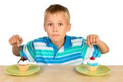 男孩和两块杯形蛋糕 库存照片