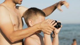 男孩和人救生员神色通过双筒望远镜 影视素材