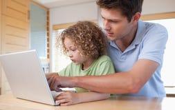 男孩和他的使用膝上型计算机的父亲 免版税图库摄影
