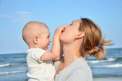 男孩和他的在海滩的母亲乐趣 图库摄影