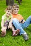 男孩和他的姐妹坐草在结构树下 库存照片