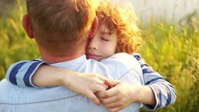 男孩和他的成熟父亲坐河岸 日落 儿子在肩膀紧紧拥抱他的父亲 股票视频