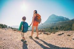 男孩和他的母亲在山的上面站立 免版税库存照片