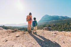 男孩和他的母亲在山的上面站立 库存图片