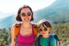男孩和他的母亲坐山的上面 库存图片