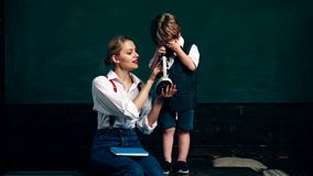 男孩和他的母亲看某事在显微镜以学校课程为背景 概念了解 影视素材