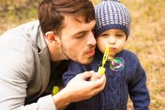 男孩和他的爸爸,吹的泡影外面 库存图片