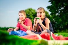 男孩和吃西瓜的女孩在一个晴天 免版税库存照片