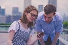 男孩和女孩一起使用一个智能手机 库存图片