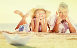 男孩和女孩一起坐沙滩 免版税库存照片