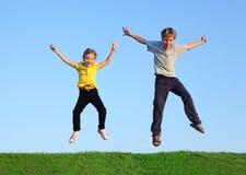 男孩和女孩一起跳在草 库存照片