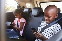 男孩和女孩一辆汽车的使用片剂和智能手机在旅行 库存照片