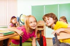 男孩和女孩互相谈话在学校 免版税库存图片