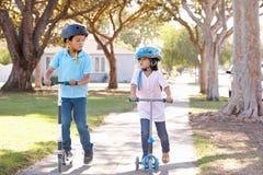 男孩和女孩佩带的安全帽和乘坐的滑行车 图库摄影