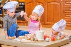 男孩和女孩和一个新出生的孩子与他们在厨师` s帽子坐厨房地板弄脏用面粉 图库摄影
