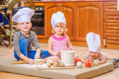 男孩和女孩和一个新出生的孩子与他们在厨师` s帽子坐厨房地板弄脏用面粉 库存照片