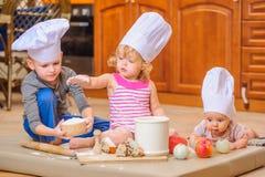 男孩和女孩和一个新出生的孩子与他们在厨师` s帽子坐厨房地板弄脏用面粉 免版税图库摄影